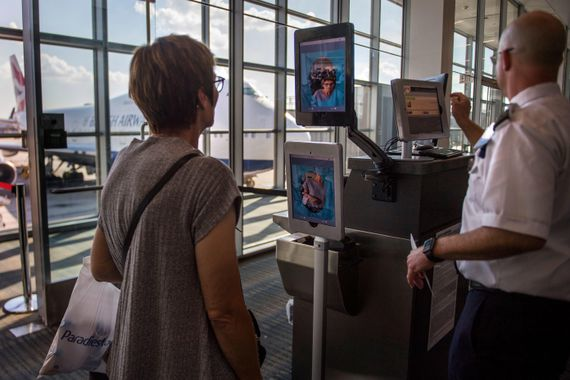 A woman stands in an airport boarding gate in front of a kiosk with two screens showing a photo of her face.